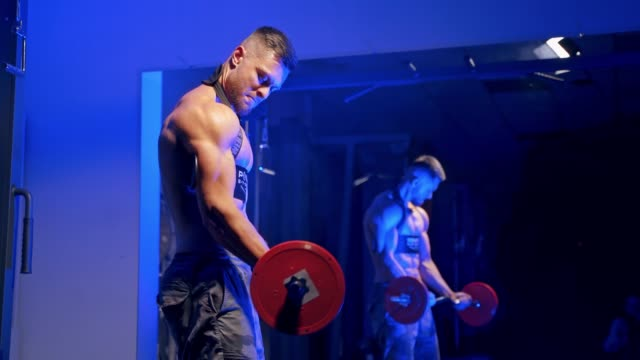 Young brutal sexy strong bodybuilder athletic fitness man pumping up barbell.