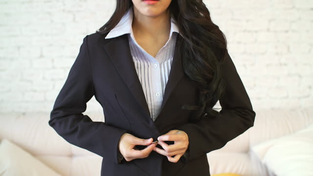 young business asian woman buttoning her suit.preparing for working in the morning. - vestirsi video stock e b–roll
