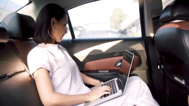 Young Business Asian Woman Working on Computer and Mobile Phone in the car.