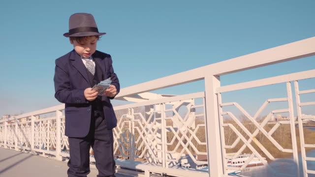 ung affärs pojke i svart kostym och hatt kastar pengar från bron. slösa pengar - spendera pengar bildbanksvideor och videomaterial från bakom kulisserna