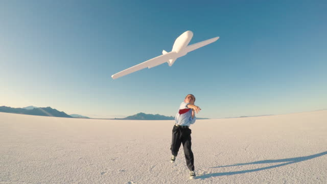Young Business Boy with Toy Airplane A young boy dressed in business attire holding a toy airplane imagines taking off with his business venture into the sky at the Bonneville Salt Flats in Utah, USA. He dreams of becoming a pilot and taking his new business to a successful future. 4K video. salt flat stock videos & royalty-free footage