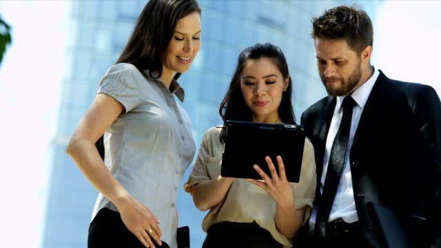 vidéos et rushes de jeunes collègues à l'aide de tablette sans fil de hot spot - book