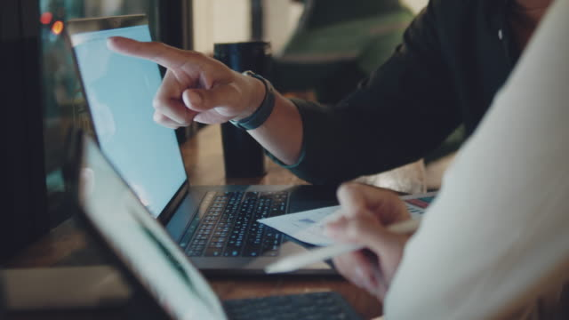 unga företag par kontrollera något på laptop och använda dokument på ett coworking utrymme på natten - brainstorming bildbanksvideor och videomaterial från bakom kulisserna
