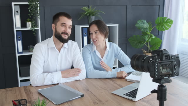 Young business couple recording new video for vlog