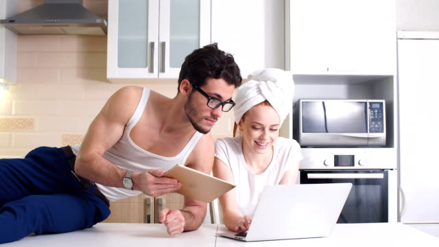 young business couple working with laptop at home in kitchen - ape operaia video stock e b–roll