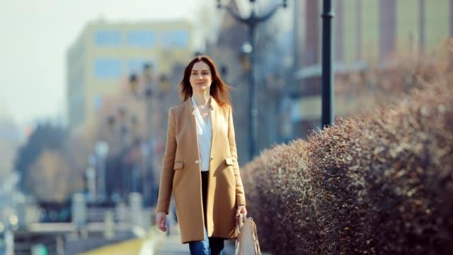 vídeos y material grabado en eventos de stock de jovencita de negocios caminando por la calle a principios de primavera. ella es feliz y disfruta de la vida. día soleado. - abrigo