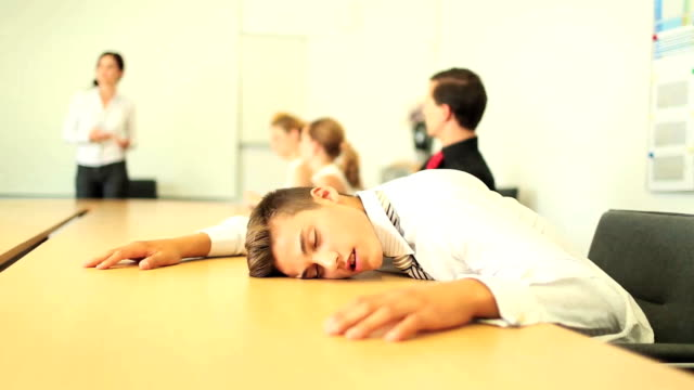 Young business man asleep on the boardroom table video