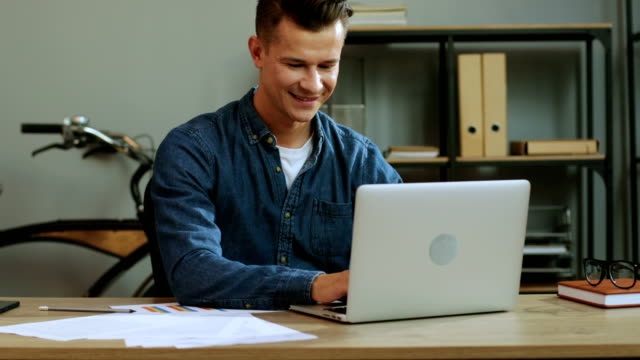 vídeos de stock e filmes b-roll de young business man in casual shirt working in the laptop in the stylish office, finishing work day and feeling so happy. - happy hour