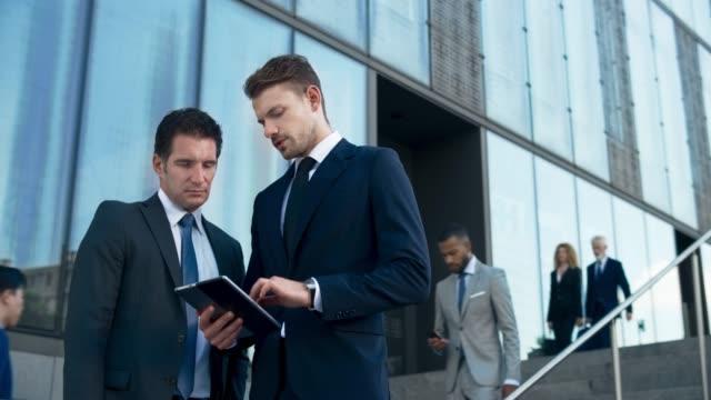 stockvideo's en b-roll-footage met ds young business man op zoek naar advies van zijn oudere collega als ze staan op de trap buiten het zakelijke gebouw - medium filmcompositietype