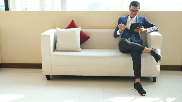 young business man use tablet on sofa video