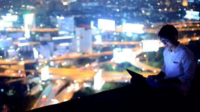 Young business man using laptop and look to cityscape, asian video