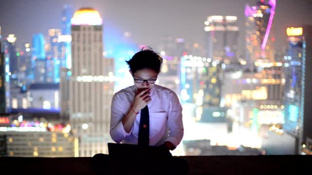 młody biznes człowiek korzystający z laptopa i spojrzeć na miasto, azjatycki - chińczycy filmów i materiałów b-roll