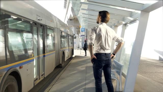 Hombre de negocios joven espera en la parada de autobús, cálida luz del sol, traje de hombre de negocios de la ciudad - vídeo