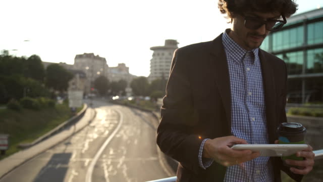 Young business man walking on city streets and drinking coffee video