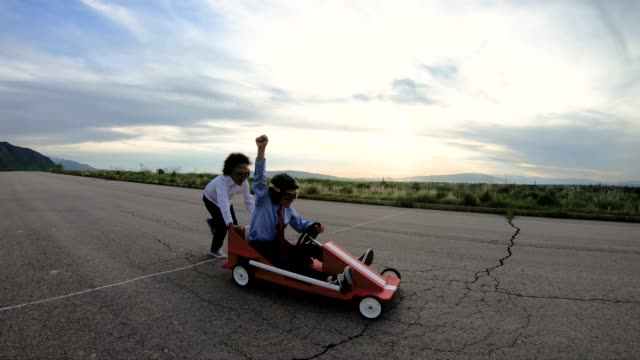 Young Business Team of Children Go Cart Race A young business girl pushes a boy dressed in business attire and race goggles in a push cart down a rural road in Utah. These business children love racing and competing and working together for the success of their business. They give a raised hand in victory at the finish line. 4K resolution video. go cart stock videos & royalty-free footage