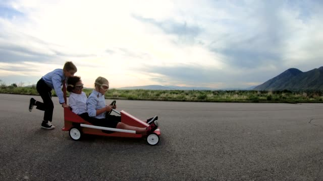 Young Business Team of Children Go Cart Race A young business boy pushes two girls dressed in business attire and race goggles in a push cart down a rural road in Utah. These business children love racing and competing and working together for the success of their business. They give a raised hand in victory at the finish line. 4K resolution slow motion video. go cart stock videos & royalty-free footage