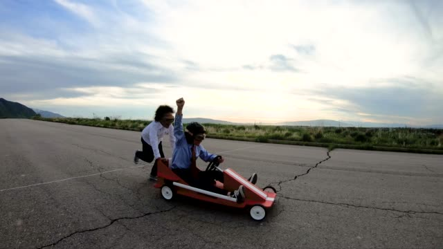 Young Business Team of Children Go Cart Race A young business girl pushes a boy dressed in business attire and race goggles in a push cart down a rural road in Utah. These business children love racing and competing and working together for the success of their business. They give a raised hand in victory at the finish line. 4K resolution slow motion video. go cart stock videos & royalty-free footage