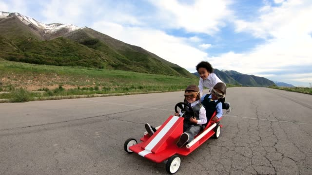 Young Business Team Races a Go Cart A young business girl pushes two boys dressed in business attire and race goggles in a push cart down a rural road in Utah. These business children love racing and competing and working together for their business. This competition gives them success at the finish line. 4K resolution slow motion video. go cart stock videos & royalty-free footage