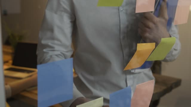 Young business team working in the office Young business team working in the office, a man is taking sticky notes on a glass wall and a woman is typing on a laptop, creative business and coworking concept post structure stock videos & royalty-free footage