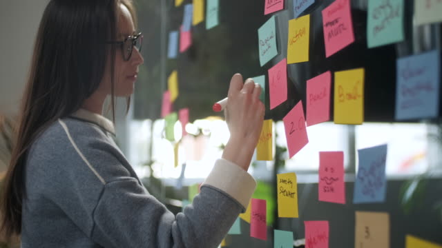 junge geschäftsfrau brainstorming. asiatische frau schreiben ideen auf haftnotizen an glaswand befestigt. business success concept - effektivität stock-videos und b-roll-filmmaterial