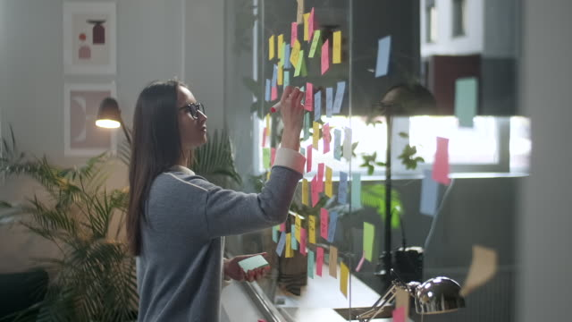 ung affärskvinna brainstorming. asiatisk kvinna skriva ner idéer på klisterlappar bifogas glasvägg. affärsframgångskoncept - tema bildbanksvideor och videomaterial från bakom kulisserna