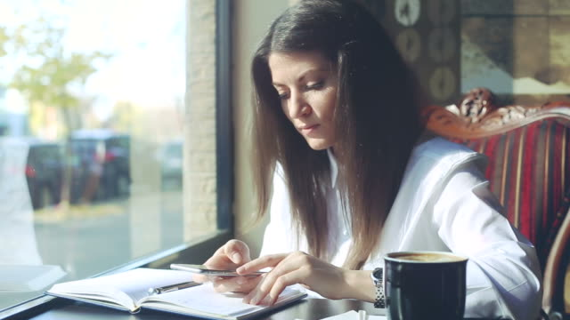 Young business woman browsing her smartphone in the coffee shop. video