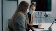 istock young business woman discussing business with her colleague working with face masks in the office during COVID-19 pandemic 1269850313