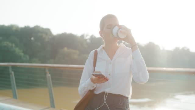 ms genç iş kadını bir akıllı telefon kullanırken gitmek için kahve içme - kulak i̇çi kulaklık stok videoları ve detay görüntü çekimi