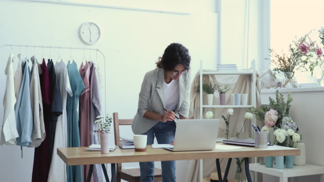 Young business woman fashion designer drawing sketch standing at workplace