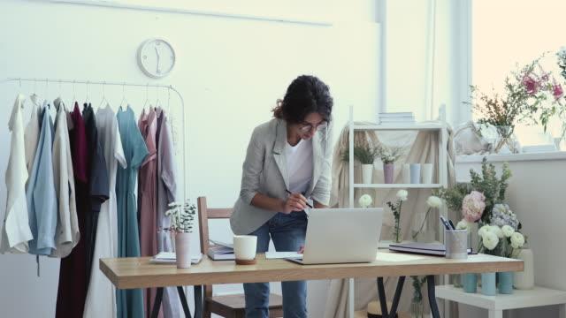 genç iş kadını moda tasarımcısı çizim kroki işyerinde ayakta - küçük stok videoları ve detay görüntü çekimi