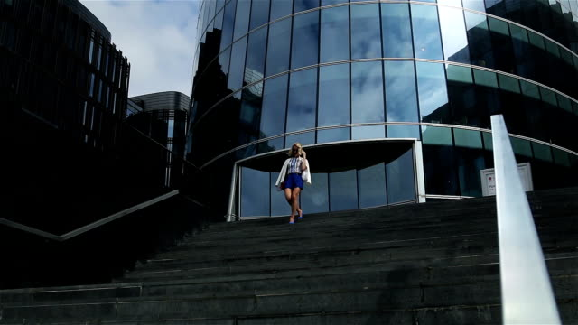 young business woman in short blue trunks down the stairs video