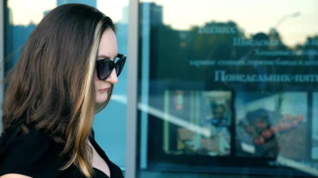 ung affärskvinna i solglasögon promenader i stad gata nära kontorsbyggnad. profil av attraktiva affärskvinna pendling till arbete. självsäker tjej att vara på väg till jobbet. slow motion närbild - kostym sida bildbanksvideor och videomaterial från bakom kulisserna