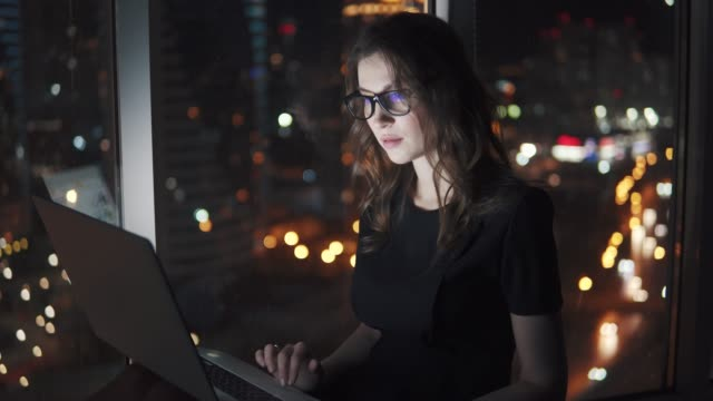 Young business woman in the light of a mobile phone screen. girl with a smartphone on the bokeh background of the night city.