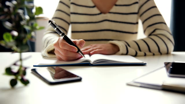 Young business woman sitting at table and writing in notebook. On table is smartphone, and tablet. Freelancer working, writing down new ideas