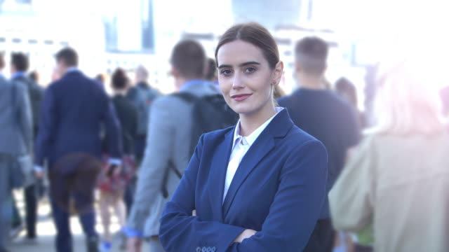 Young business woman standing out from the crowd. Time lapse. Time lapse of a young woman wearing a suit her hair sided back standing arms crossed looking at camera, crowds of commuters walk past behind her. focus on foreground stock videos & royalty-free footage