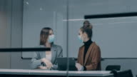 istock young business woman using laptop and discussing business with her colleague working with face masks in the office during COVID-19 pandemic 1269998497