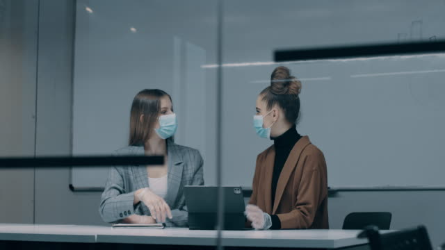 young business woman using laptop and discussing business with her colleague working with face masks in the office during COVID-19 pandemic