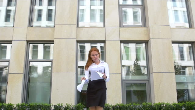 young business woman with papers flying up, slow motion video