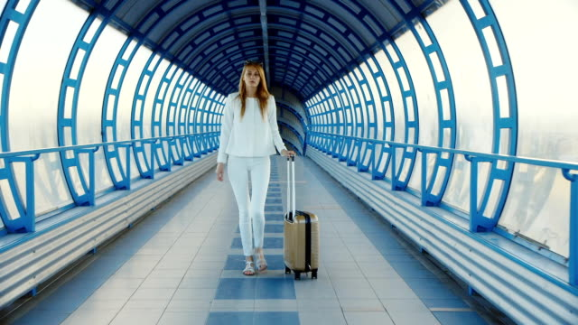 young business woman with travel bag on wheels is on the transition from the terminal at the airport or train station - donna valigia solitudine video stock e b–roll