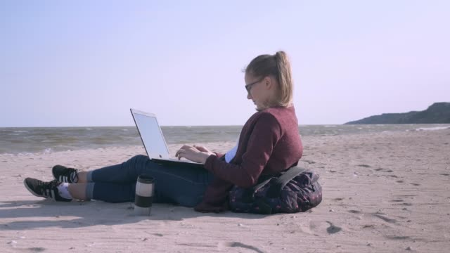 young business woman working on laptop on the beach at sunset freelance job online traveler freelancer working with tablet computer on the beach young business woman working on laptop on the beach at sunset freelance job online traveler freelancer working with tablet computer on the beach minority groups stock videos & royalty-free footage