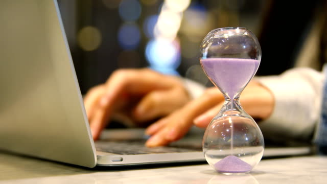 Young business woman working with hourglass
