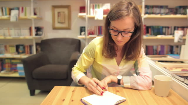 Young business woman writing notes in a bookstore. video