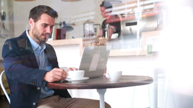 Young businessman at a table in a cafe using laptop computer video