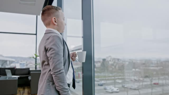 ung affärsman pojke med kaffe promenader till office fönster, realtid - kostym sida bildbanksvideor och videomaterial från bakom kulisserna
