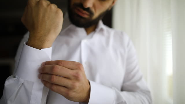 Young businessman buttoning sleeve while standing near window in hotel room Young bearded businessman buttoning sleeve while standing near window in hotel room businesswear stock videos & royalty-free footage