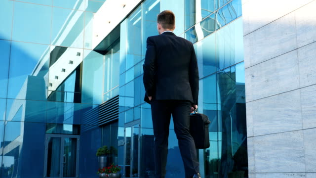 young businessman commuting to work. confident guy in suit being on his way to office. business man with a briefcase walking in city street near modern building. slow motion rear back view close up - podążać za czynność ruchowa filmów i materiałów b-roll