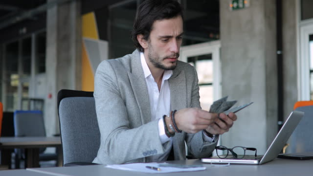 Young businessman counting money in office