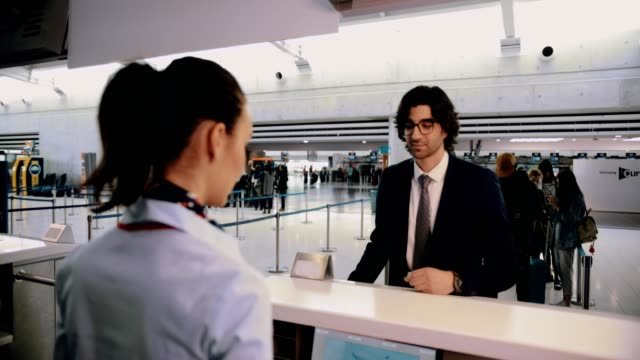 Young businessman doing check-in at airport before international business travel Airline attendant giving young businessman passport and boarding pass at airport check-in counter passport stock videos & royalty-free footage