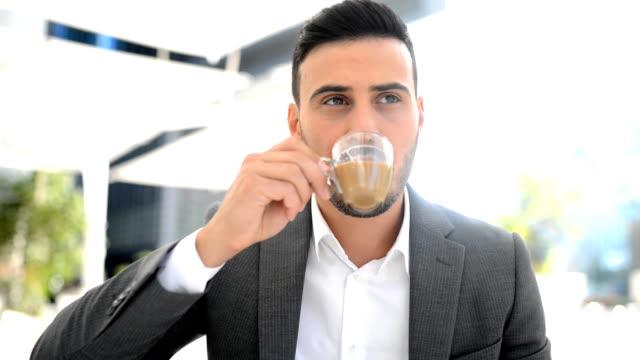 young businessman drinking an espresso coffee in a cafe - espresso filmów i materiałów b-roll
