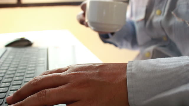 young businessman drinking coffee and  using  laptop for business work  in blurred focus video